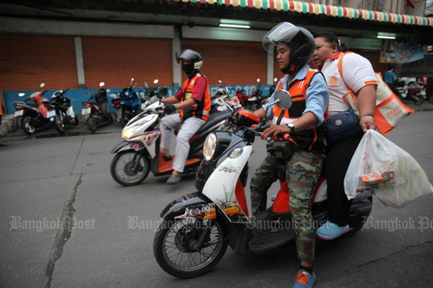 A motorcycle taxi picks up a customer in Bangkok. (Bangkok Post file photo)