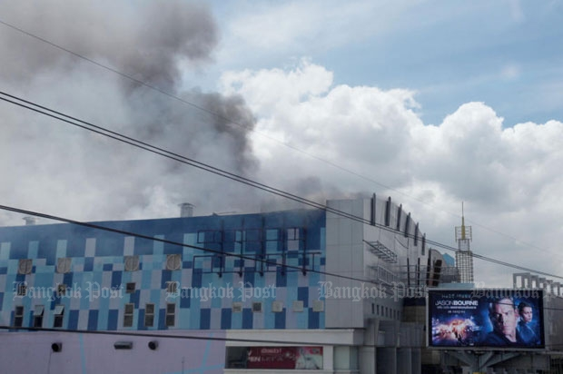 Fire engulfs Major Cineplex Pinklao shortly before noon on Thursday. (Photo by Kitja Apichonrojarek)