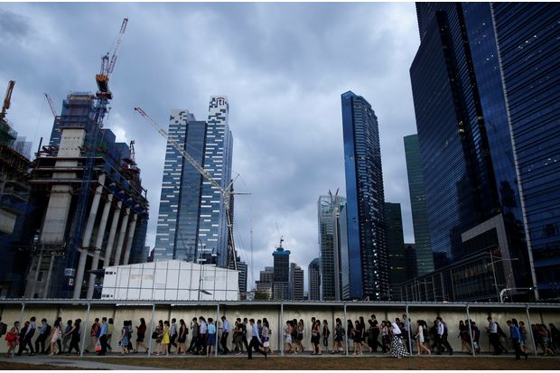 Office workers walk to the train station during evening rush hour in the financial district of Singapore on March 9, 2015. (Reuters file photo)