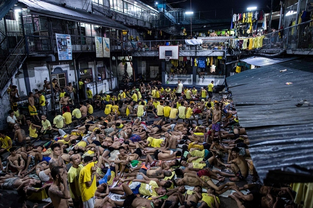 Inmates sleep on the ground of an open basketball court inside the Quezon City jail in Manila. The jail, built to house 800 prisoners, now has 3,800. (AFP Photo)