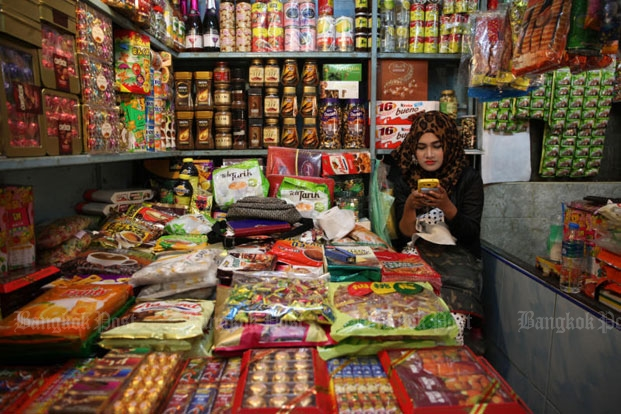 A woman uses her mobile phone while tending her shop in Kimyong market in Songkhla's Hat Yai district in February 2016. (Bangkok Post file photo)
