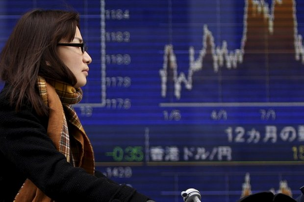 A woman rides her bicycle past a Tokyo electronic board showing the latest currency exchange rates. (Reuters photo)