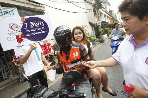 Huay Kwang district officials hand out a sheet to a taxi motorcycle and his passenger on Pracharat Bumphen Road on Wednesday to promote the charter referendum. (Photo by Pornprom Satrabhaya)