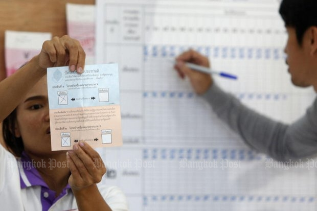 A poll official counting votes Sunday at the polling station in Rajavinitbangken School in Laksi district unfolds a ballot showing 'Yes' for both the draft charter and the extra question on the appointed senate. (Photo by Pattarapong Chatpattarasill)