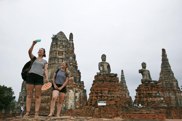 Tourists take selfies at Wat Chai Wattanaram in Ayutthaya province. The National Broadcasting and Telecommunications Commission plans to track foreign visitors' movements in the country around the clock with special SIM cards. (Photo by Seksan Rojjanametakun)