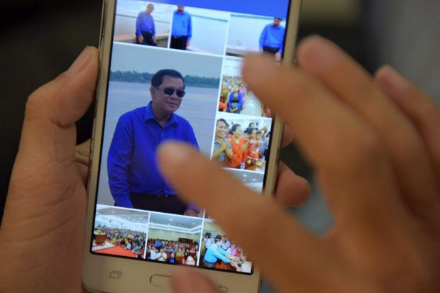 A Cambodian man in Phnom Penh browses his smartphone displaying photos of Cambodian Prime Minister Hun Sen on the leader's Facebook page. (AFP photo)