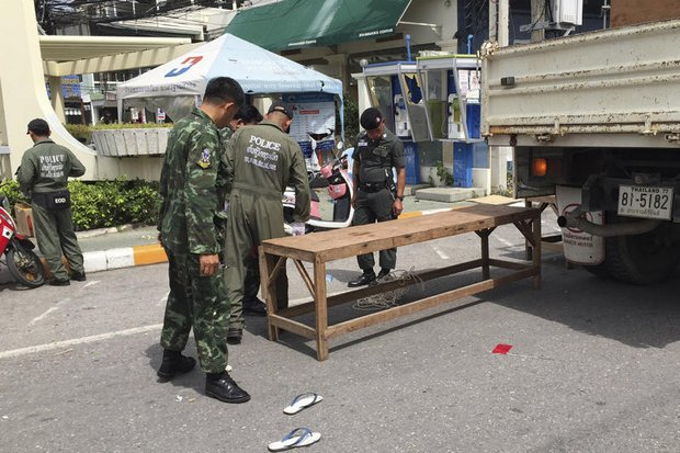 Police and explosives experts block off access in downtown Hua Hin on Friday morning to investigate the bomb blasts, as the police chief requested everyone to stay in their homes. (AP photo)