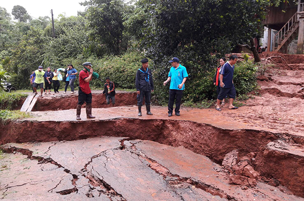 Local officials examine a section of subsided road in Chalerm Phra Kiat district of Nan province on Monday morning, (Photo: Rarinthorn Petcharoen)
