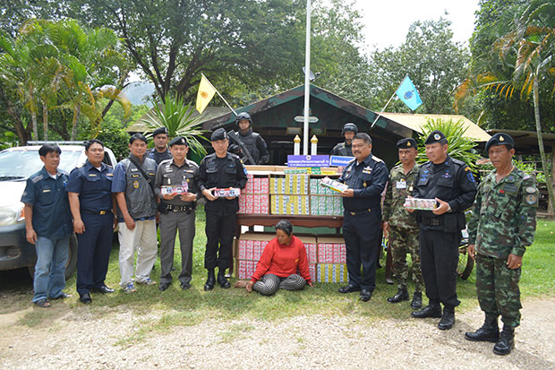 Smuggled cigarettes falsely packaged as Thai brands, worth about 6.6 million baht, and the Cambodian woman suspect are shown at a media briefing in Sa Kaew's Khlong Hat border district on Monday afternoon. (Photo by Sawat Ketngarm)