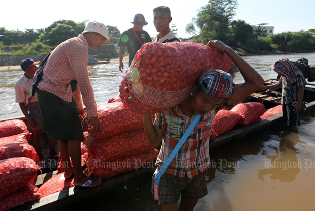 Workers unload fresh produce from a boat on Moei River, which is the natural border between Thailand and Myanmar in Tak's Mae Sot district. (Bangkok Post file photo)