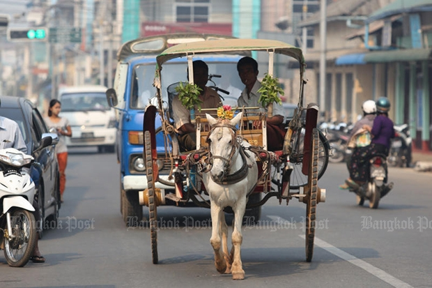 Horse-drawn rickshaws are still a popular means of transport in Dewei, but more cars are rapidly appearing on the roads. The Myanmar government will lift import restrictions on automobile parts from Sept 1. (Bangkok Post file photo)