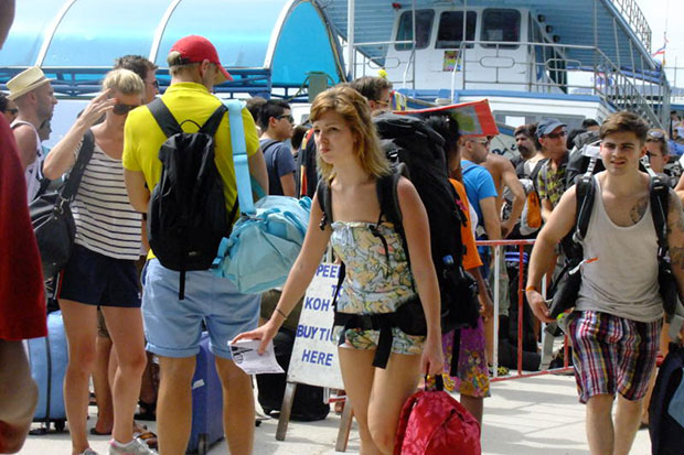 Tourists arrive at Koh Phangan from the mainland Surat Thani. Authorities have stepped up security ahead of the full-moon party on the island on Thursday. (File photo by 