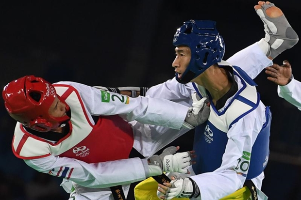 Thailand's Tawin Hanprab (L) competes against China's Zhao Shuai in the men's taekwondo gold medal bout in the -58kg category as part of the Rio 2016 Olympic Games, on August 17, 2016. Zhao Shuai took the gold with a narrow 6-4 victory.  AFP PHOTO / Kirill KUDRYAVTSEV