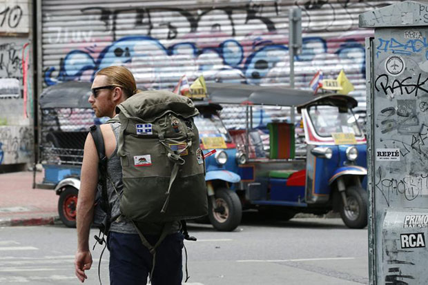 A tourist waits on a street in Bangkok on Thursday. The University of the Thai Chamber of Commerce says last week's bomb and arson attacks will result in fewer visitors to the country. (EPA photo)