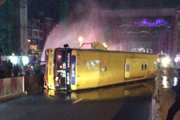Emergency services spray water to contain the natural gas fuel leaking from the engine of the Por Or 68 bus after the driver crashed it on Ratchada-Tha Phra Road on Wednesday night.  (Photo via FM 91 Traffic pro Facebook)