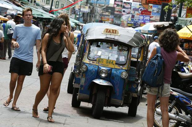 Foreign tourist walk on a road next a tuk-tuk at a popular tourist area of Khaosan road on Aug 14, 2016. (EPA photo)