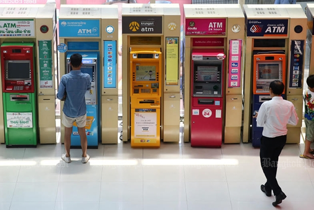 People use commercial bank ATMs in a department store. The machine second from right is operated by the Government Savings Bank. (Bangkok Post file photo)