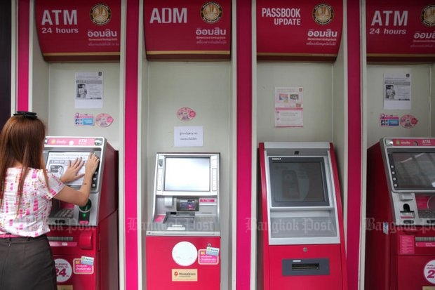 An employee posts paper 'out-of-service' notices on Government Savings Bank ATMs after cyber-thieves armed with malware got them to spew 12 million baht in cash like a casino jackpot. (Photo by Wichan Charoenkiatpakul)