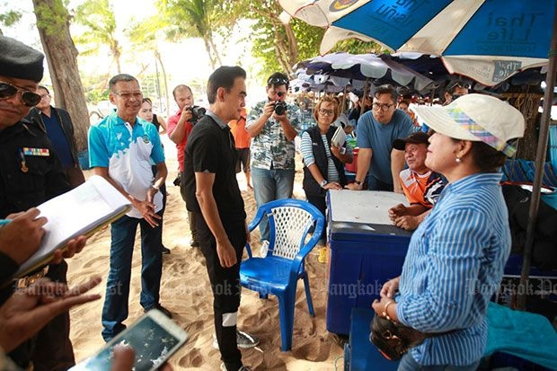 A deckchair and umbrella rental operator (right) whose staff were accused of chasing away tourists for setting up their own mats tries to explain her side of the story to officials at Jomtien beach on Saturday. (Photo by Chaiyot Pupattanapong)