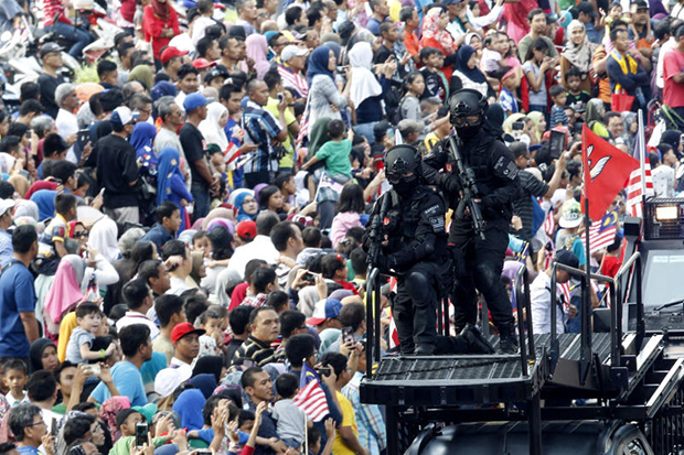Well-armed Malaysian Special Task Force police dressed in black stand guard during the 59th National Day celebrations at  Independence Square in Kuala Lumpur on Wednesday. (AP Photo)