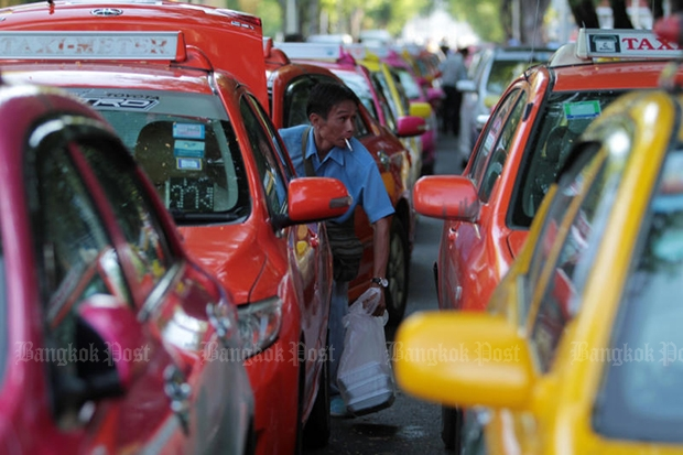A taxi driver smokes while his car is parked at the Royal Plaza, during a gathering to call for state help ahead of the government's increase in the price of LPG for vehicles in September 2013. (Bangkok Post file photo)