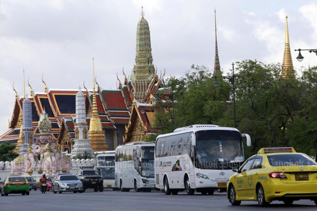 Tour buses pass the Grand Palace on Rattanakosin Island in Bangkok. Authorities are considering four underground parking sites to ease congestion in the area. (Photo by Apichart Jinakul)