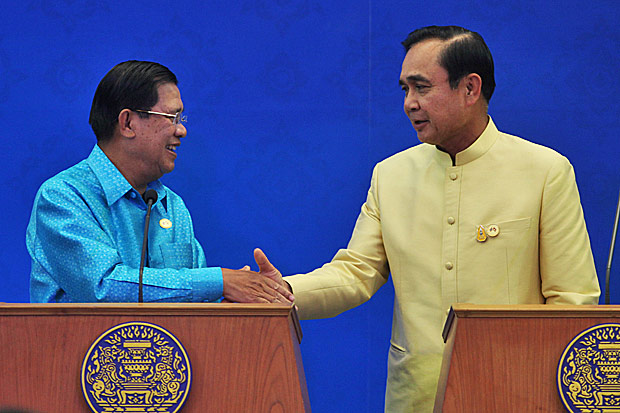 Cambodian Prime Minister Hun Sen and Thai Prime Minister Prayut Chan-o-cha shake hands before a ceremony at Government House in Bangkok last December. Photo by Thiti Wannamontha
