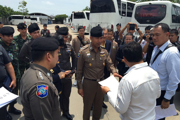 Tourist police commander Surachet Hakpan, centre, leads authorities to seize the tour buses of OA Transport Co in Lat Krabang district of Bangkok on Friday. (Tourist police photo)