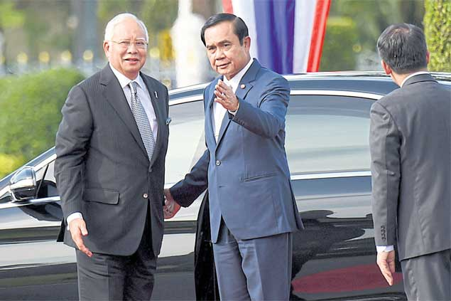 Prime Minister Prayut Chan-o-cha welcomes his Malaysian counterpart Najib Razak outside Thai Khu Fa Building before the 6th Malaysia-Thailand Annual Cooperation meeting at Government House on Friday. (Government House photo)