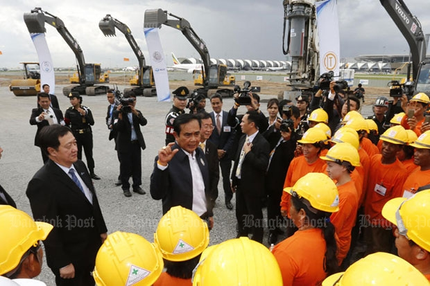 Prime Minister Prayut Chan-o-cha makes a point to airport staff on the site allocated for the second-stage expansion of Suvarnabhumi airport on Wednesday. (Photo by Pattanapong Hirunard)