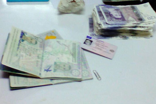 An image shows the passports of the arrested men and forged 20-pound notes. (Photo by Suphapong Chaolan)