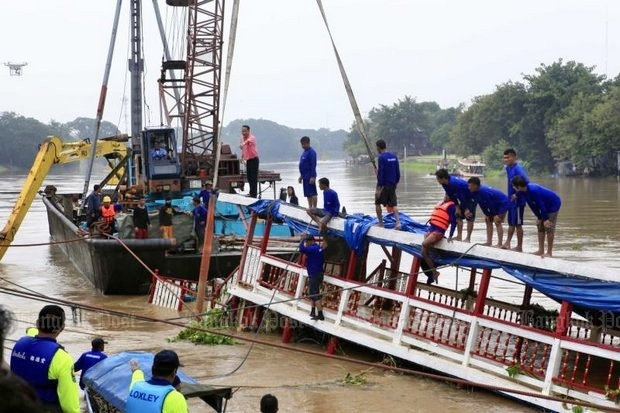 A large crane took several hours Tuesday to raise the sunken Sombat Mongkolchai Tabtim passenger boat which sank near the bank of the Chao Phraya River in Ayutthaya on Sunday. (Photo by Apichart Jinakul)