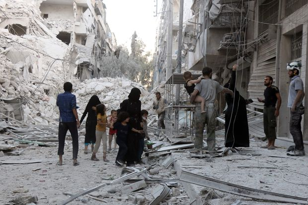 A Syrian family leaves the area following a reported airstrike on Friday, on the al-Muasalat area in the northern Syrian city of Aleppo. (AFP photo)