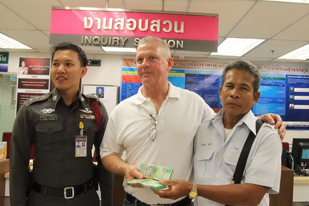 Wimol Treepat (right), a taxi driver, returns the money left in his taxi to his passenger David Collinson at the police unit of Suvarnabhumi airport (photo by Sutthiwit Chayutworakan)