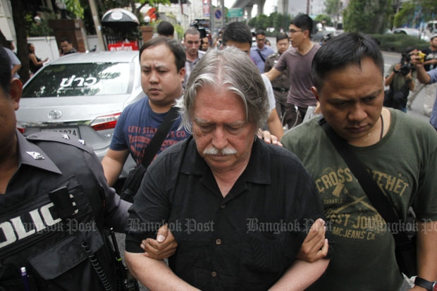 Police lead away James Douglas Eger, one of the three foreigners, arrested following the raid on an alleged passport-forgery operation in Phra Khanong district of Bangkok on Friday. (Photo by Pattarapong Chatpattarasill)