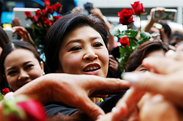 Former prime minister Yingluck Shinawatra greets supporters as she arrived at the Supreme Court on Aug 5, 2016 for a trial on the rice subsidy scheme during her administration. (Reuters photo)