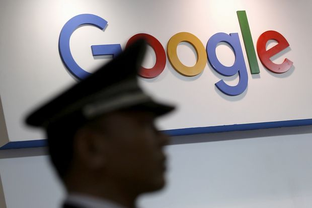 A security guard keeps watch as he walks past a logo of Google in Shanghai on April 21, 2016. (Reuters photo)