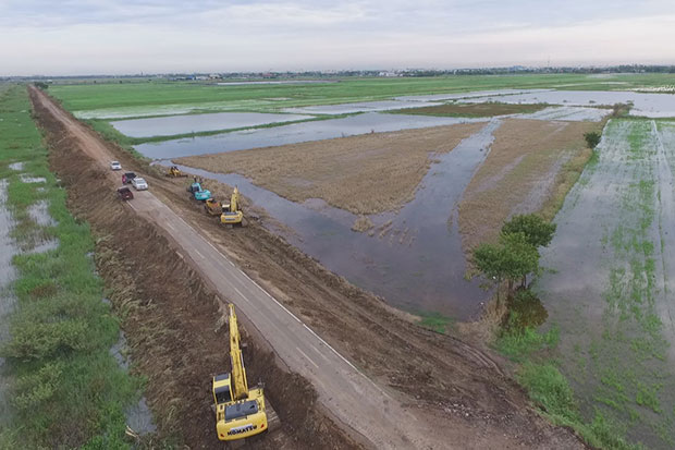 A water barrier to industrial parks in Ayutthaya is under repair to cope with rising water from the Chao Phraya River. (Photo by Sunthorn Pongpao)
