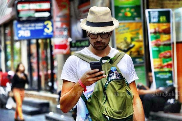 A tourist checks his phone on Silom Road, probably unaware that the National Broadcasting and Telecommunications Commission (NBTC) wants to issue him a special SIM card so he can be closely tracked and monitored. (Photo by Tanaphon Ongarttragoon)