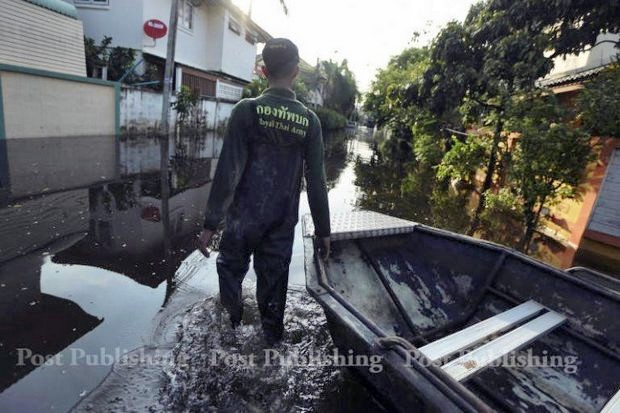 An army relief worker contemplates a flooded soi in northern Bangkok. The next several weeks are crucial if Bangkok is to remain dry from the weather trifecta: run-off from the North, heavy, daily downpours and the annual high tides. (Post Today photo)