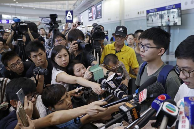 Pro-democracy activist Joshua Wong (second right) speaks to media after arriving at Hong Kong airport from Bangkok on Wednesda. (AP photo)