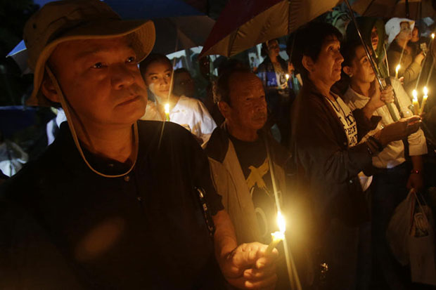 Activists hold lighted candles at Thammasat University before dawn on Thursday, as they gathered to mark the 40th anniversary of the Oct 6, 1979 killings. (AP photo)