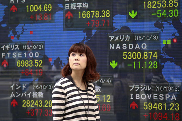 A woman walks past an electronic stock indicator of a securities firm in Tokyo. Southeast Asian markets rose on Thursday, floowing stronger Asian peers. (AP photo)