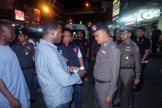 Metropolitan police commissioner Sanit Mahathavorn checks the documents of tourists on Nana Road, Bangkok, early Saturday morning. (Royal Thai Police photo)