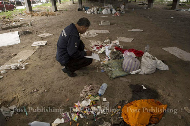 An officer from the Crime Suppression Division collects evidence at the crime scene under the Lat Phrao intersection flyover on Sunday. (Photo by Tanaphon Ongarttrakul)