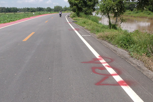 """Chai Nat residents whose home are flooded spray-paint a Thai word meaning """"reserved"""" on an embankment road as they plan to build shelters on it. (Photos by Chudate Seehawong)"""