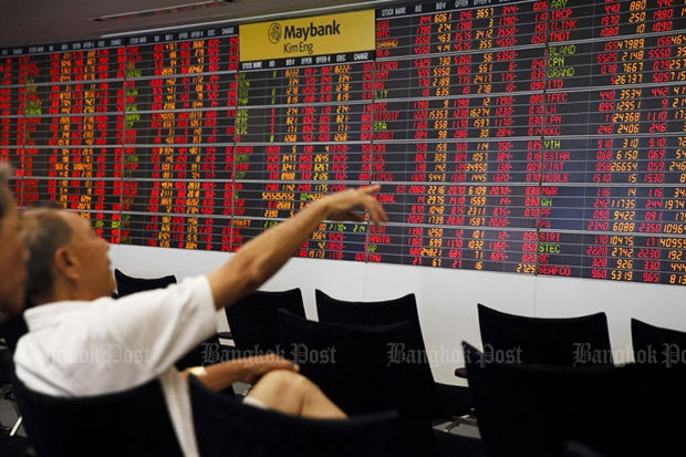 A trader looks at an electronic stock display showing plunging share prices on Monday. (Photo by Seksan Rojjanametakul)