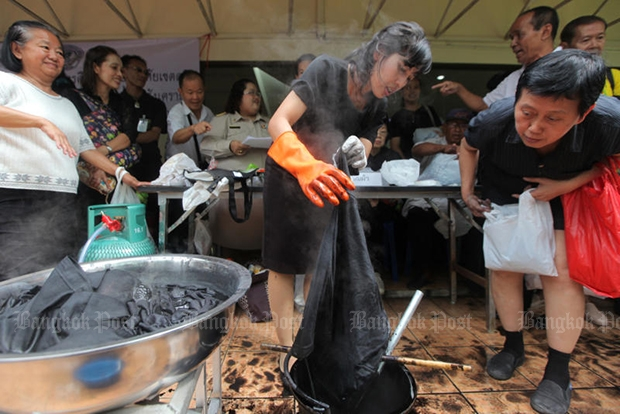 Officials from Office of the Non-formal and Informal Education demonstrate how to dye clothes black at the Education Ministry on Monday. The service is free. (Photo by Wichan Charoenkiatpakul)