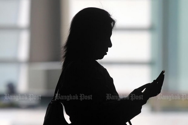 A woman uses her smartphone inside a Bangkok bank, once of millions of people who depend on big corporations to keep her personal information secure. (Photo by Seksan Rojjanametakun)