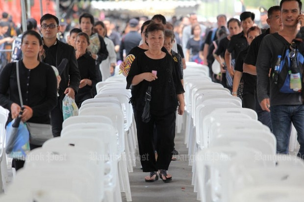 The mourners move through security, trying to follow the rules on dress, comportment, speech, facial expression as they pop up formally and via social media. (Bangkok Post photo)